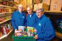 Volunteers Bill Newall and Isdale Anderson and Eagles Wings Trust founder Mike Cordiner in the food store