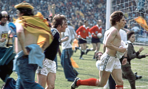 Happier times for Willie Donachie (right) and Kenny Dalglish as they run from the invading Tartan Army after Scotland beat England 2-1 at Wembley in 1977