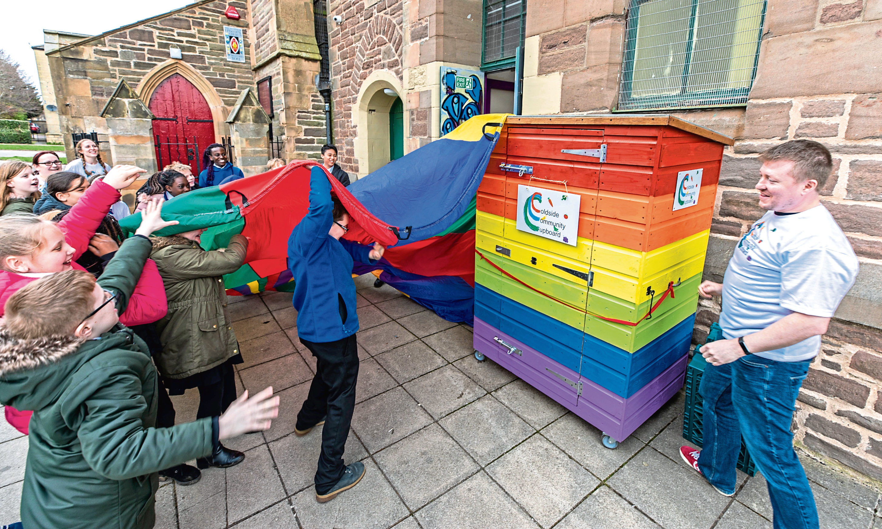 Children from Our Lady's Primary School unveil the Coldside Community Cupboard at the Maxwell Centre.