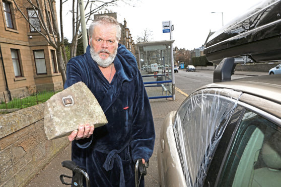 Kenneth Hill with the rock that was put through the window of his car, which belonged to his late mother.