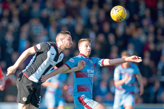 Andrew Nelson of Dundee challenges for the ball with Mateo Muzek of St Mirren