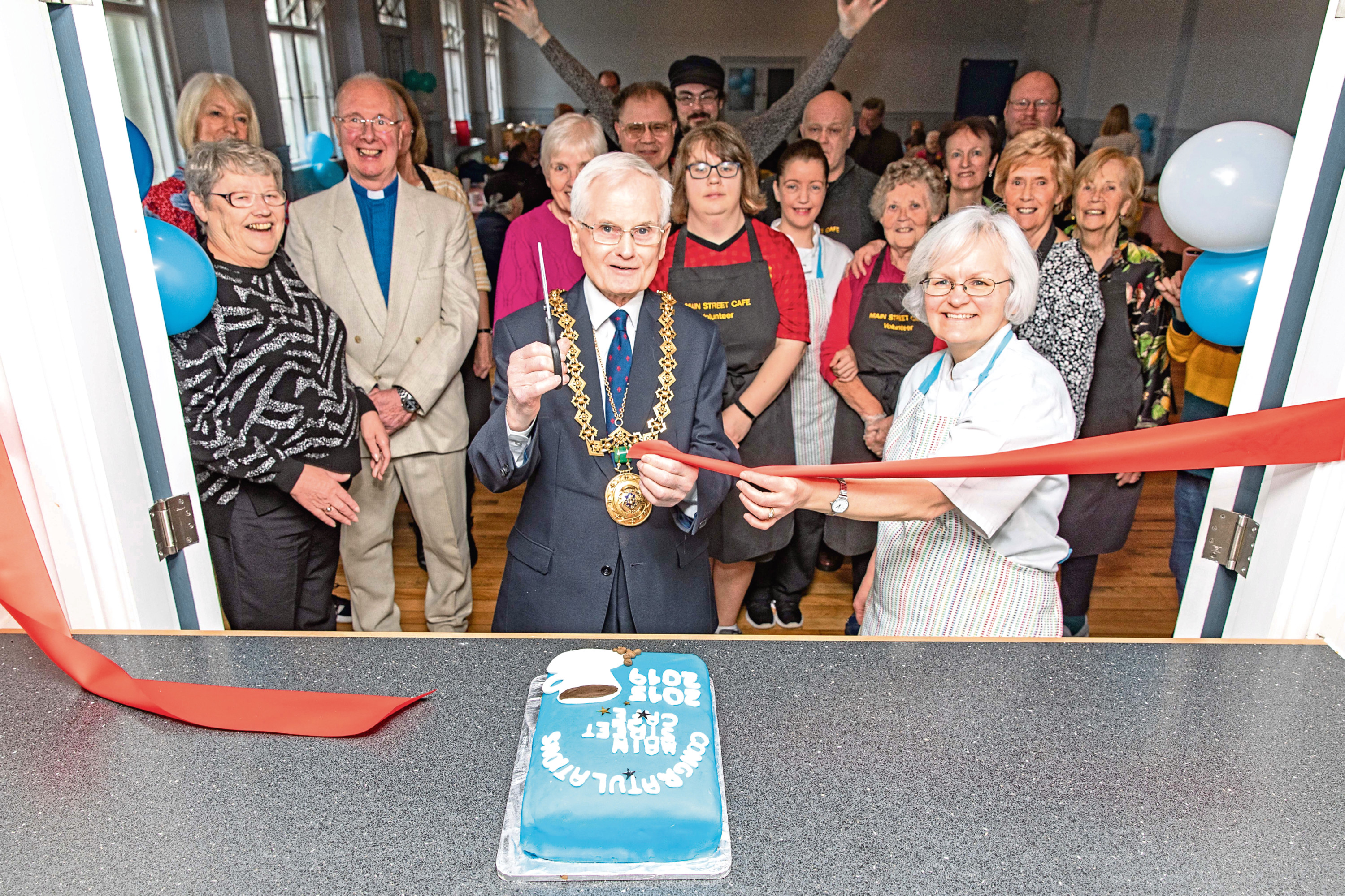 n THE lord provost cuts the ribbon helped by Sarah (right) as volunteers from the cafe look on.