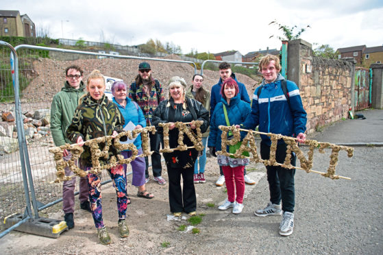 Mourners at the memorial event for Halley's Mill which was demolished without proper planning permission in May last year. They laid a wreath constructed from cardboard and hand-sewn burlap jute flowers.