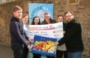 A £5,000 cheque from Cash for Kids given to Dundee Bairns representatives.