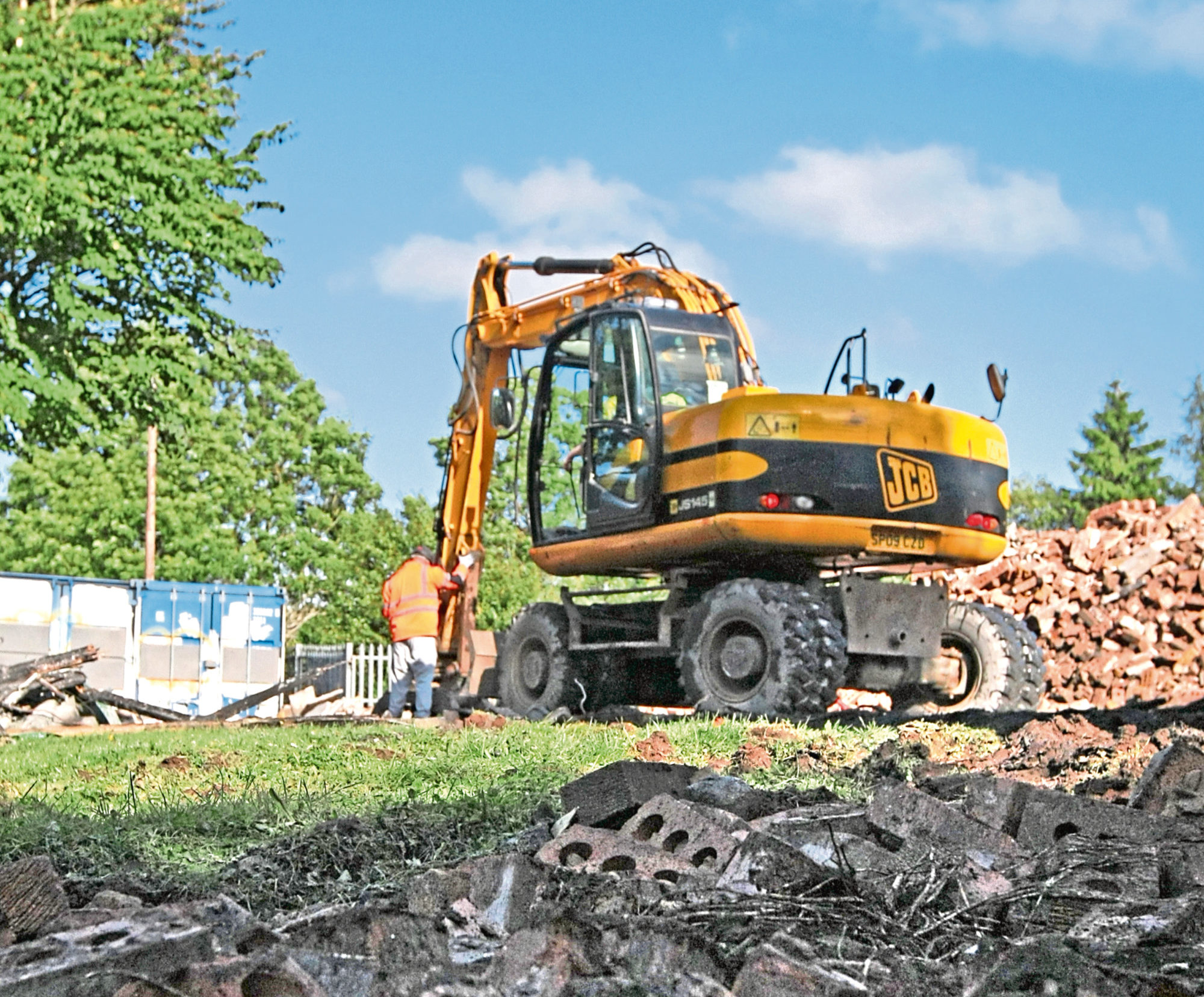 A digger at work on the ruined buildings