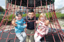Trey Banks, 4, and his cousin Alice McLoughlan, 4, have fun on the climbing frame with Bilal Ahmed from the mosque