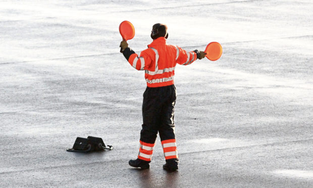 A worker at Dundee Airport prepares for a flight to land.