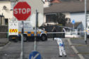 """Police forensic officers at the scene in Londonderry, Northern Ireland, where 29-year-old journalist Lyra McKee was shot and killed when guns were fired and petrol bombs were thrown in what police are treating as a """"terrorist incident"""""""