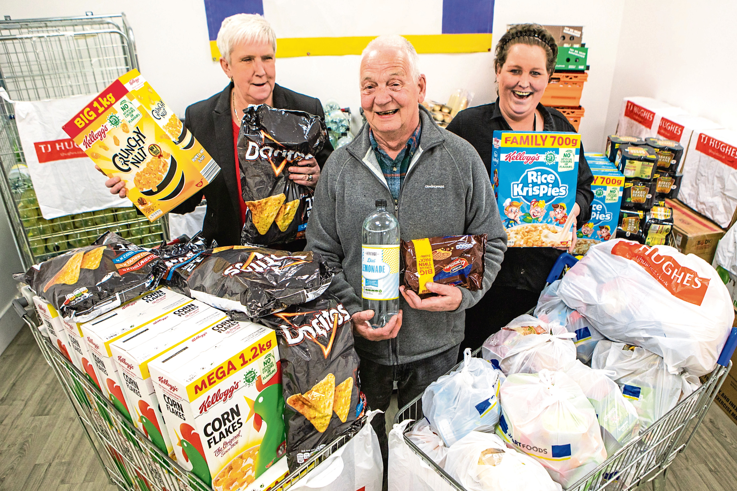 Picture shows in the centre is Chic Lowe (volunteer with Trussell Trust) alongside Ann Whyte (left, TJ Hughes Store Manager) and Kerry Sands (right, TJ Huhges Team Leader). TJ Hughes, Wellgate Centre, Dundee.
