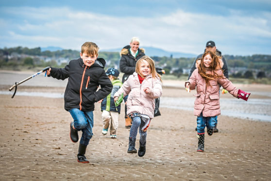 John (8), Sophie (5), and Jessica (9) Morris race to pick up litter in the successful beach clean-up at the Barry Buddon Training Camp
