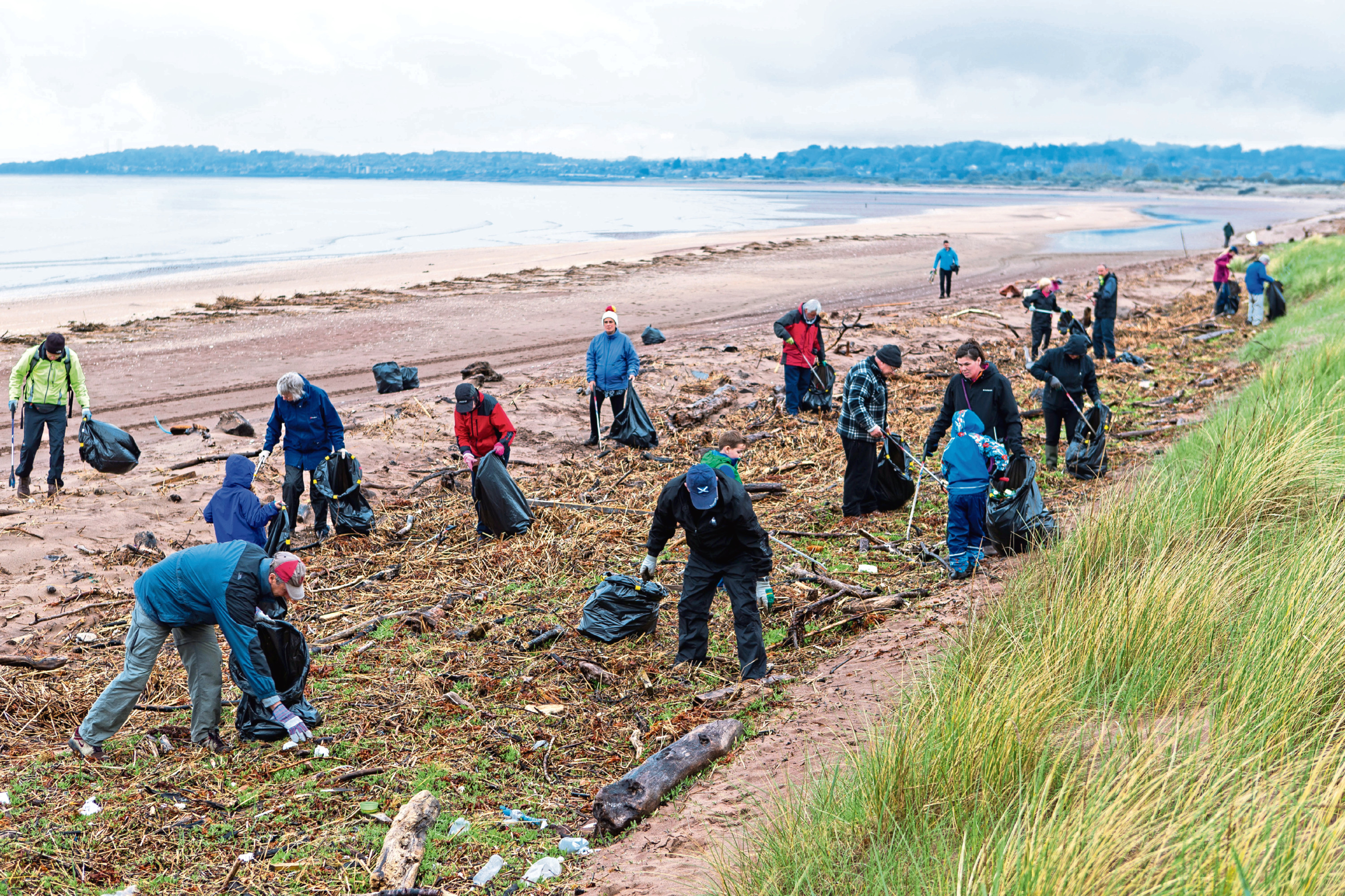 Volunteers get stuck in at Barry Buddon beach last year.