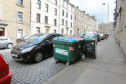 Cars are parked in front of Eurobins on the street, with the potential of causing obstruction to emergency vehicles
