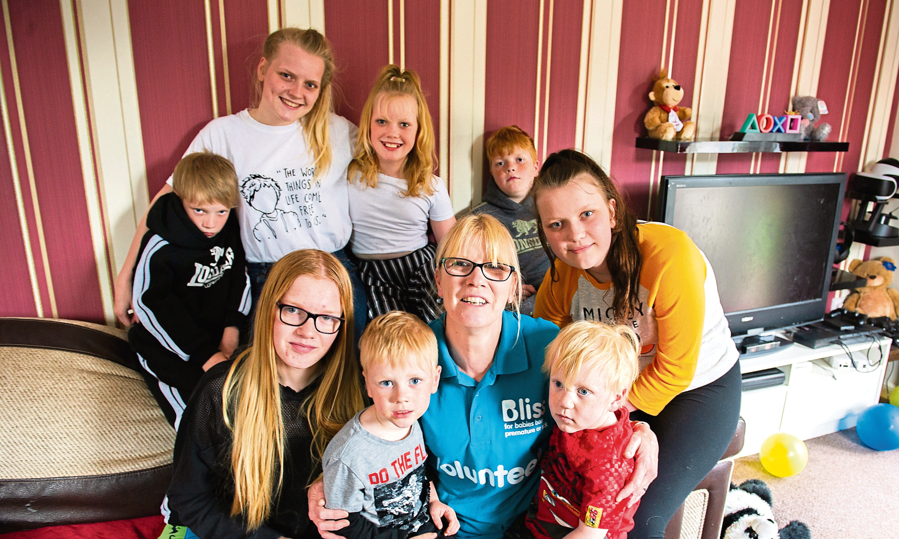 Heather Esplin has had 10 premature babies and still has eight living at home with her. Picture shows: back - left to right - Owen, Tamara, Robyn, and James; front - Imogen, Alan, Heather Esplin, Issac and Dana