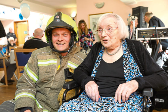Ella Low celebrating her 100th birthday at Turriff Care Home in Dundee with firefighter Chris Proctor, Red Watch, Kingsway Fire Station