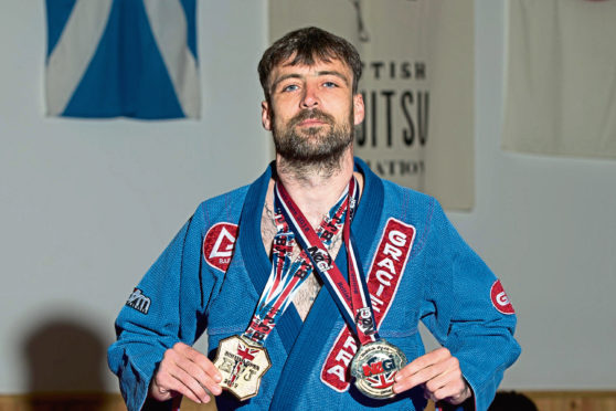 Darren Ferguson pictured with the medals from his two Jiu Jitsu British Open wins, medals are the No Gi British Open won by Darren in December and the GI British Open won on 10th May 2019.