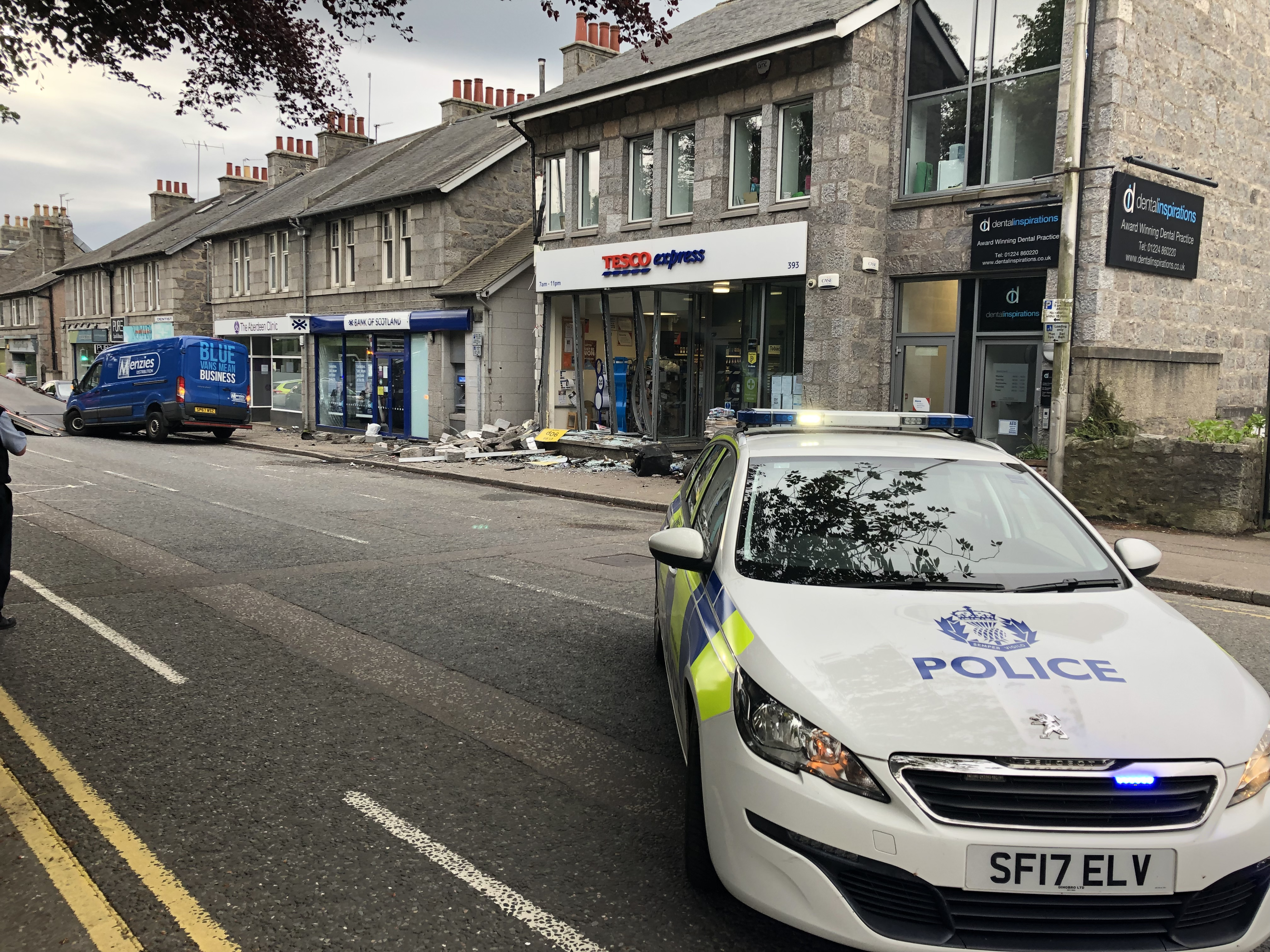 Police at the scene, with the damaged van and shop in the background.