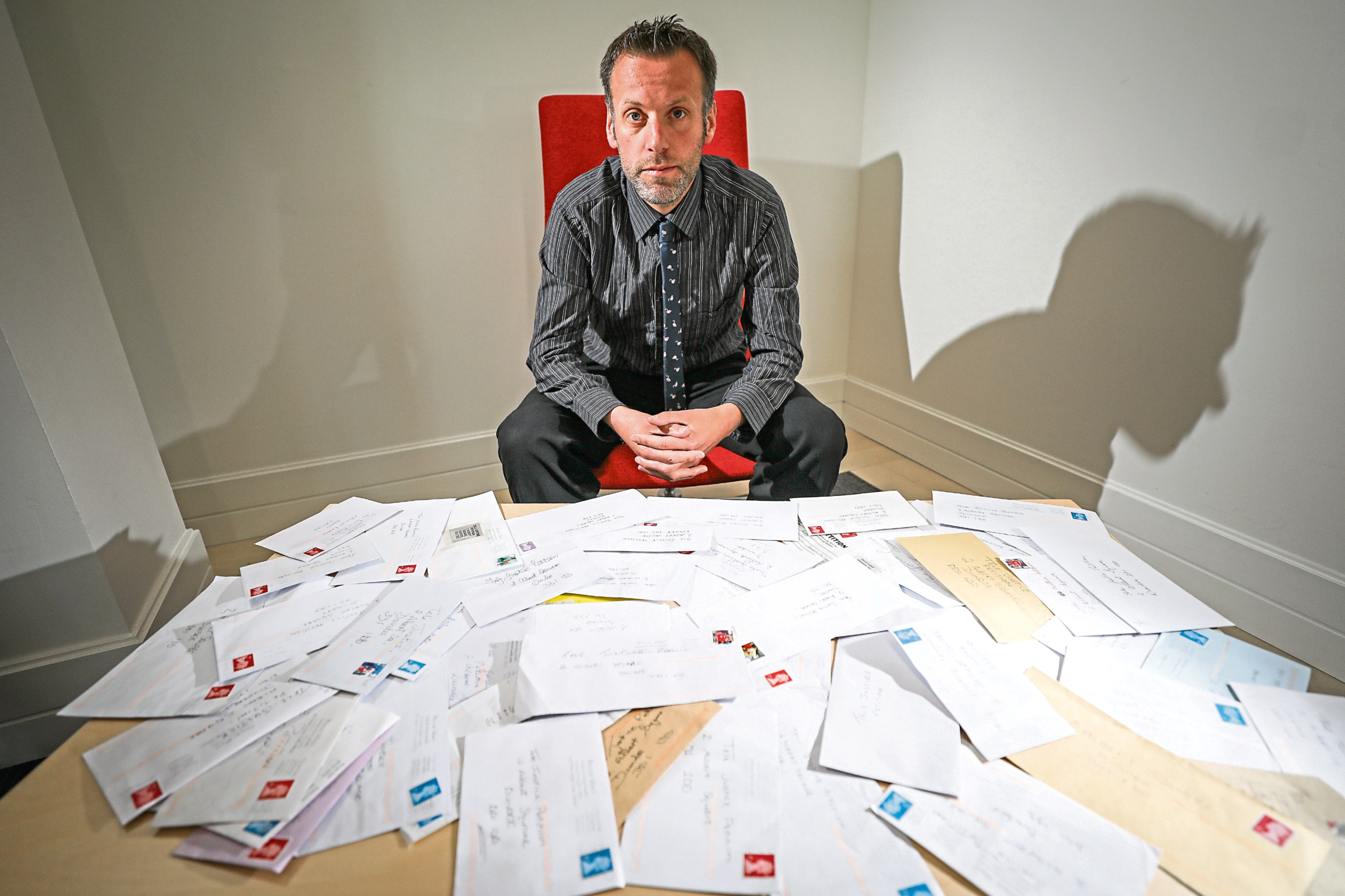 Tele editor Dave Lord with some of the letters received through the post, backing the Our Kids Need Justice campaign.