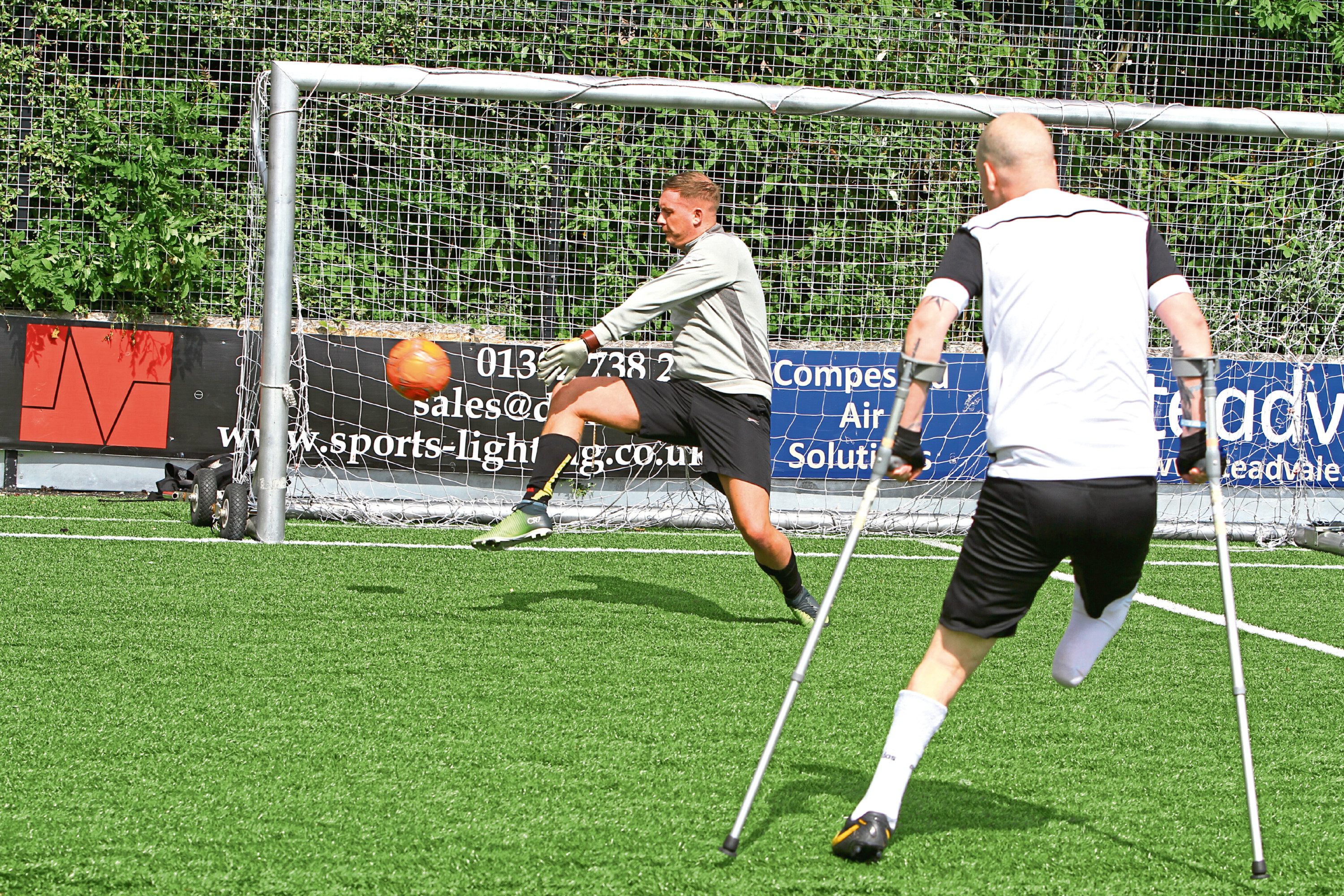 Rob Wilson firing in a shot with Steven Tully in goal, at the Amputee Football Programme training session at the GA Arena in Dundee.