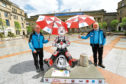 Dundee City Centre Ambassadors Andy Mackay, left, and Dave Barrie giving the Oor Rabbie Rides Again Wullie shelter from the showers, in City Square.