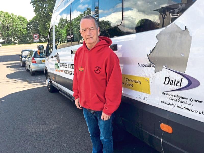 Ben Gibson beside the damaged Dundee Wanderers van.