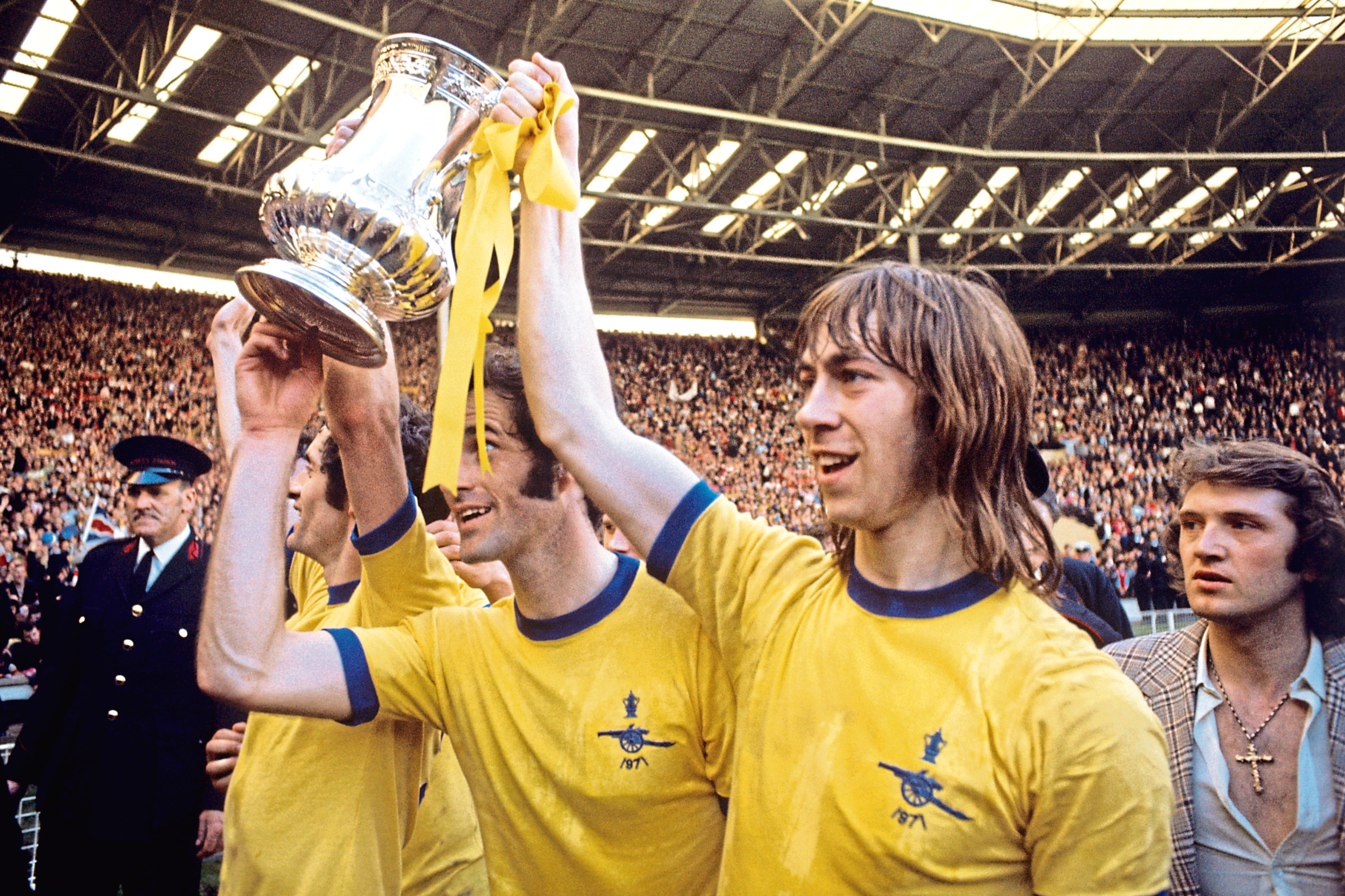Arsenal's captain Frank McLintock, George Graham and Charlie George with the FA cup after Arsenal beat Liverpool 2-1 in  the final at Wembley Stadium.