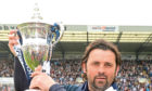 Dundee manager Paul Hartley celebrates with Scottish Championship trophy.