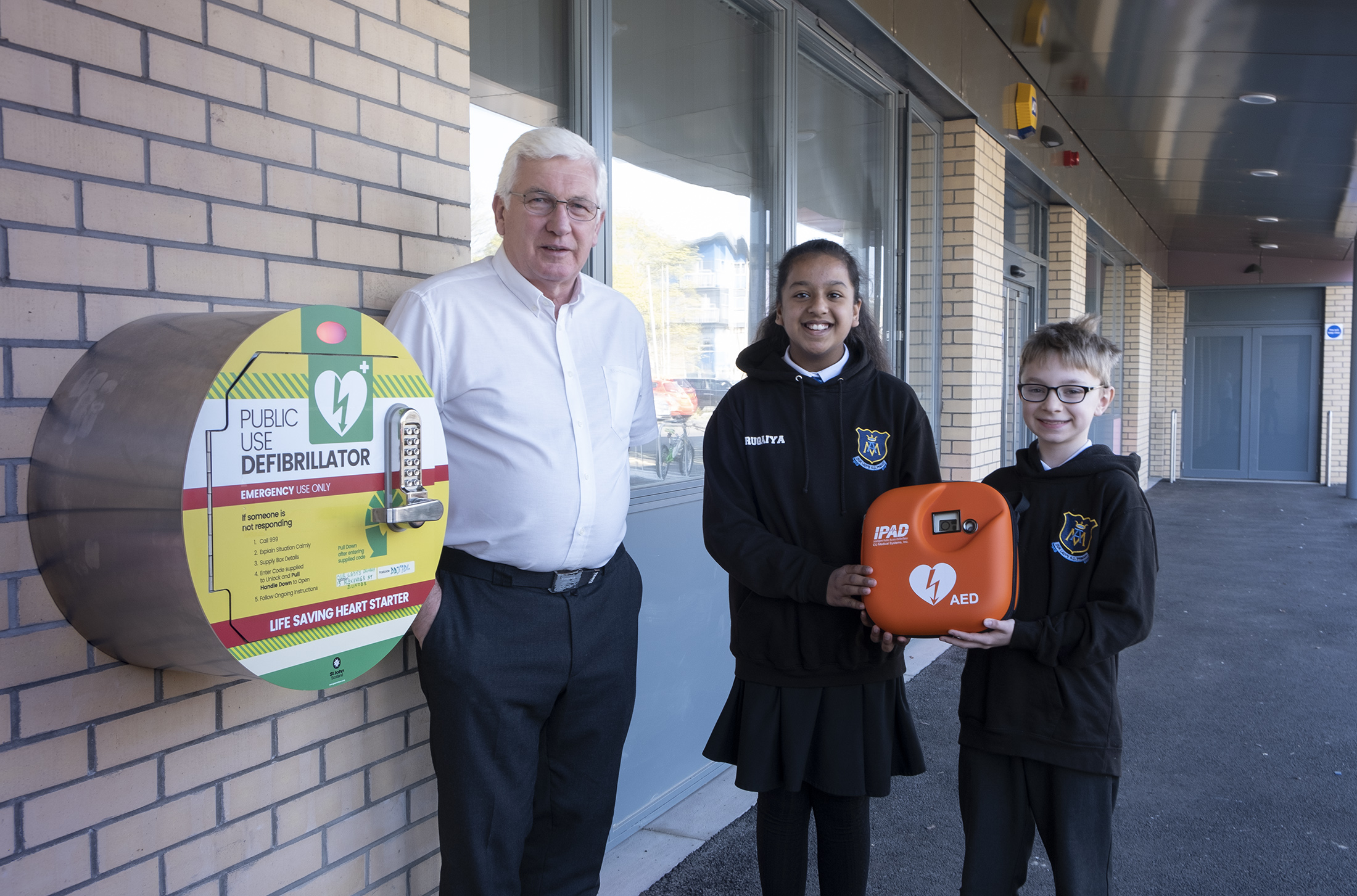 Ged Cashley suffered a heart attack at Dundee Ice Arena and his life was saved when his friends used a defibrillator to restart his heart. He is pictured at the installation of a defibrillator at Our Lady's RC Primary School in Dundee, with pupils Ruqaiya Anwar and Tobiasz Nowinski.