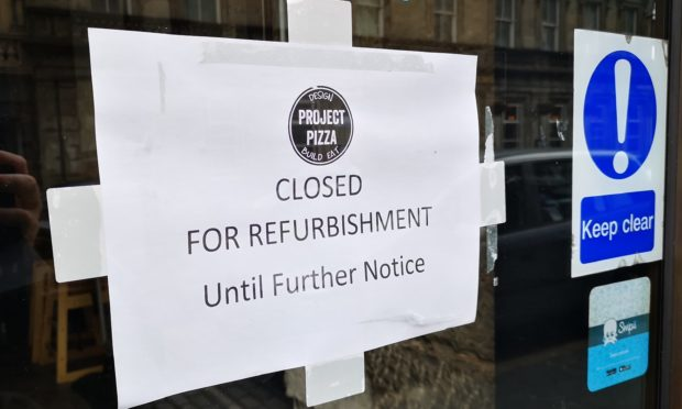 The sign on the door of Project Pizza.