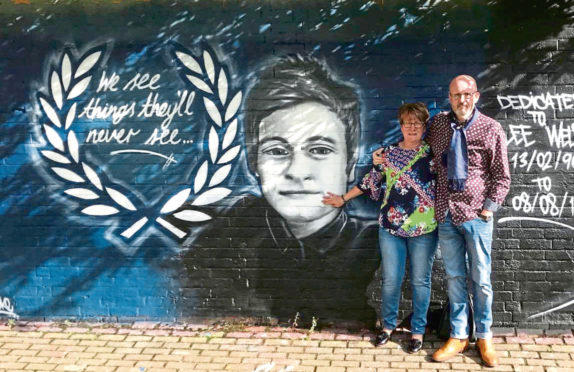 Lee Welsh's parents, Phil Welsh and Lesley Nicoll, next to a mural painted in Lee's honour.