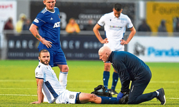 Ness receiving treatment during Dundee's game against Cove Rangers.