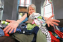 Volunteer Joyce Reid with some of the clothes that were donated to the Gate Church Carbon Saving Project earlier this year.