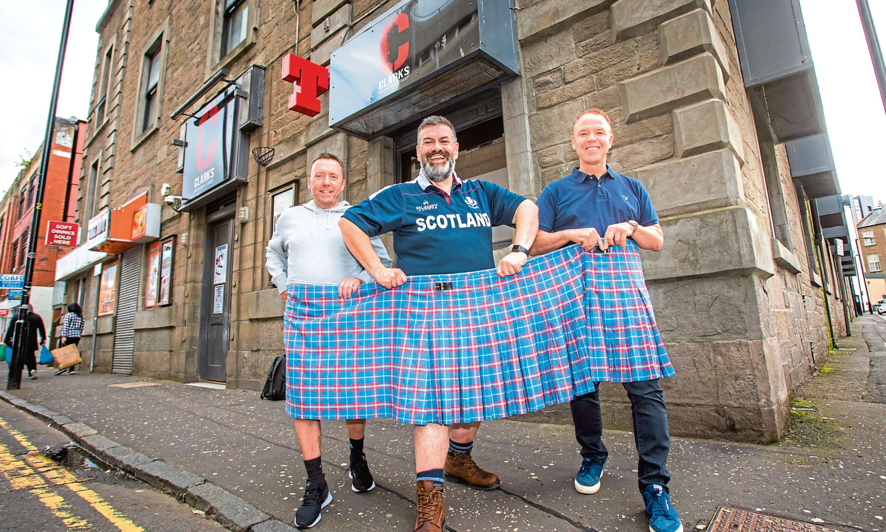 From left: Scott Clark, Tom Urie and Gus Robb with the kilt that used to fit Tom before he lost weight.