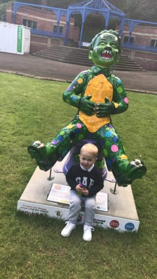 Parker Brunton, 2, from Dundee with his favourite statue in Balgay Park, Wullieosaurus.