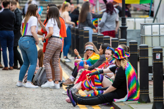 Pride revellers mix as they make their way through the busy town square.