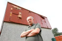 Peter Brady beside some of the damaged cladding on his house.