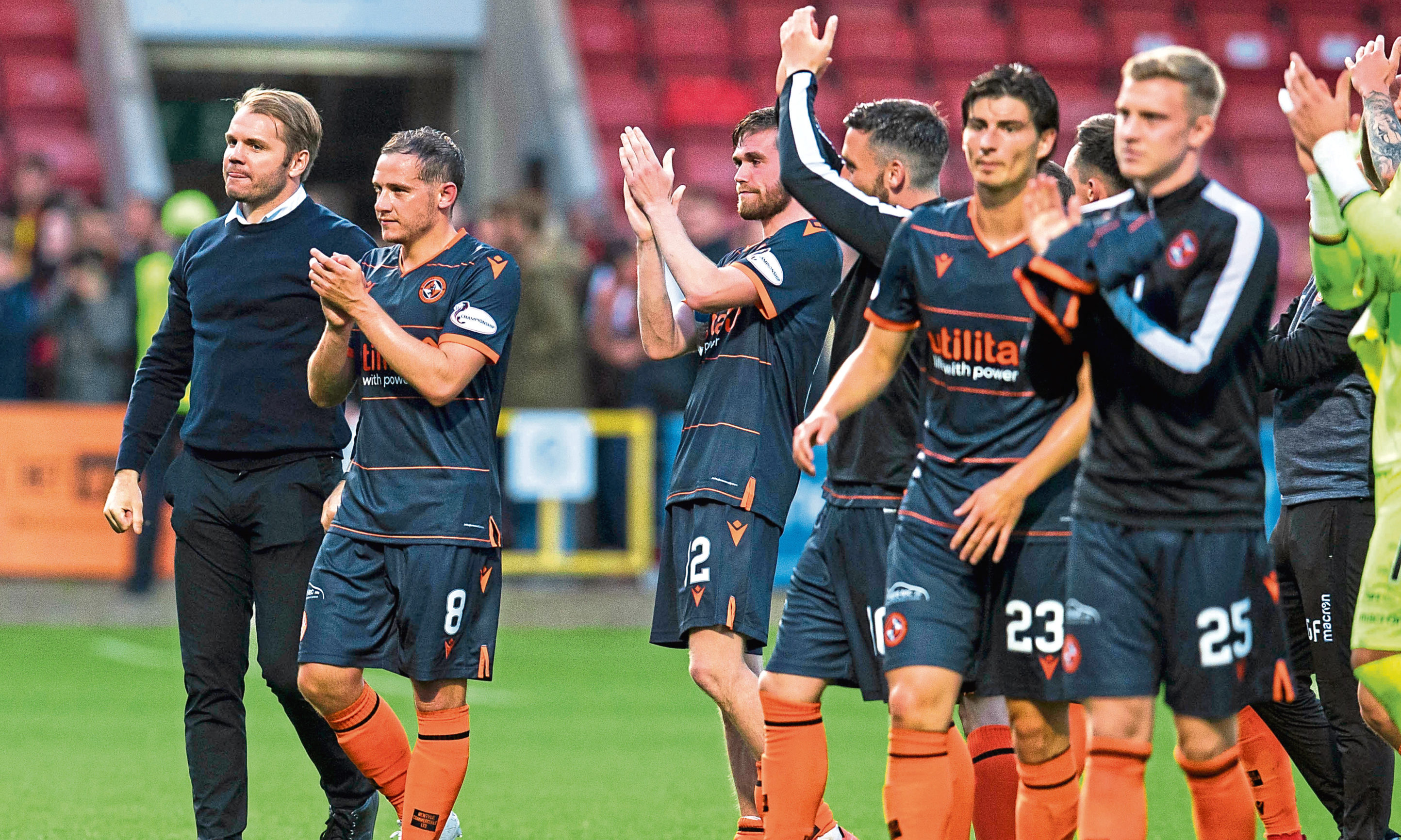 The Dundee United players celebrate with their supporters at full-time.
