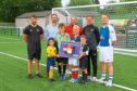 Representatives from clubs at the Dundee East Community Sports Hub, at Whitton Park today, with the new defibrillator.