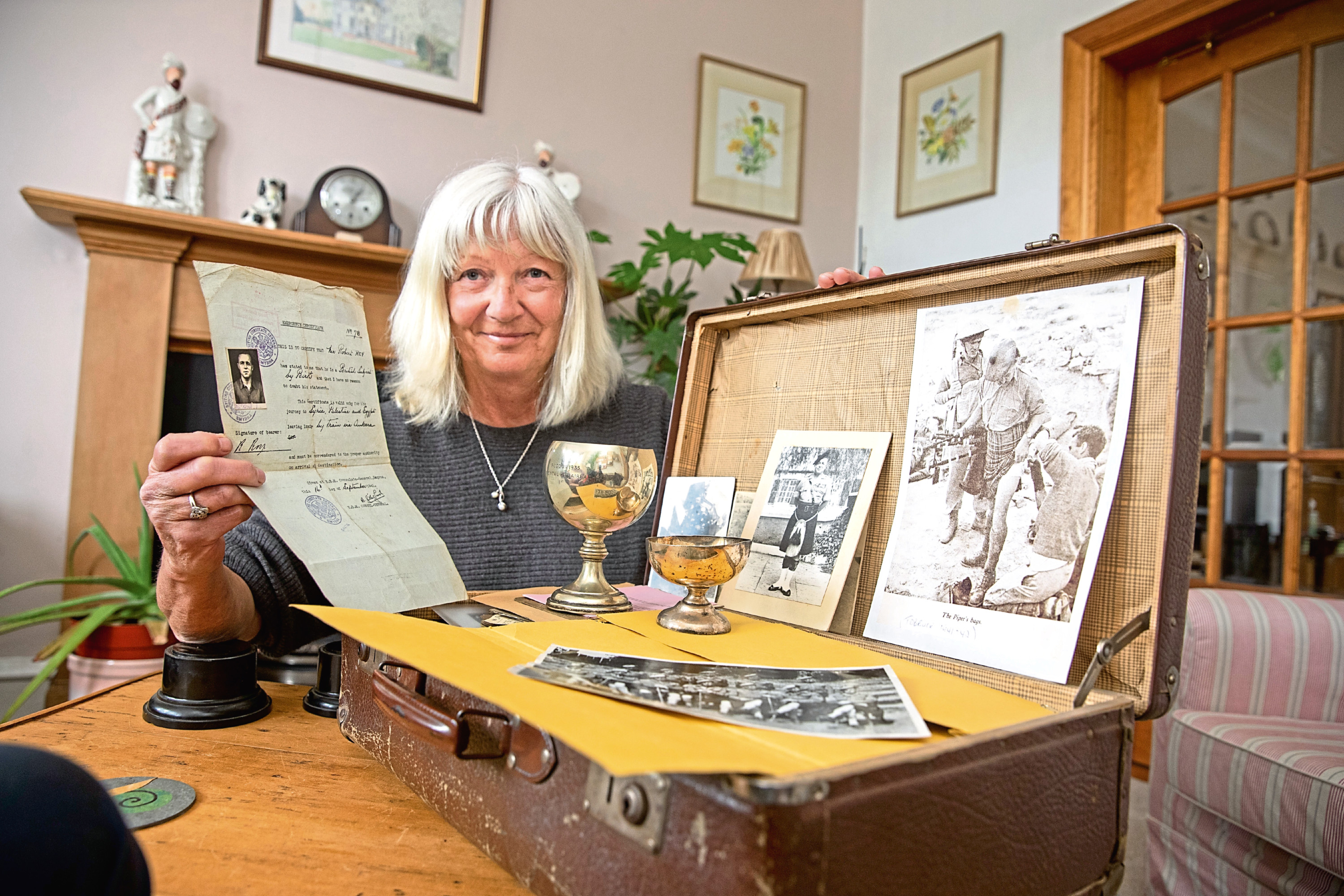 Alice with a suitcase of photo's trophies and moments of her fathers life.