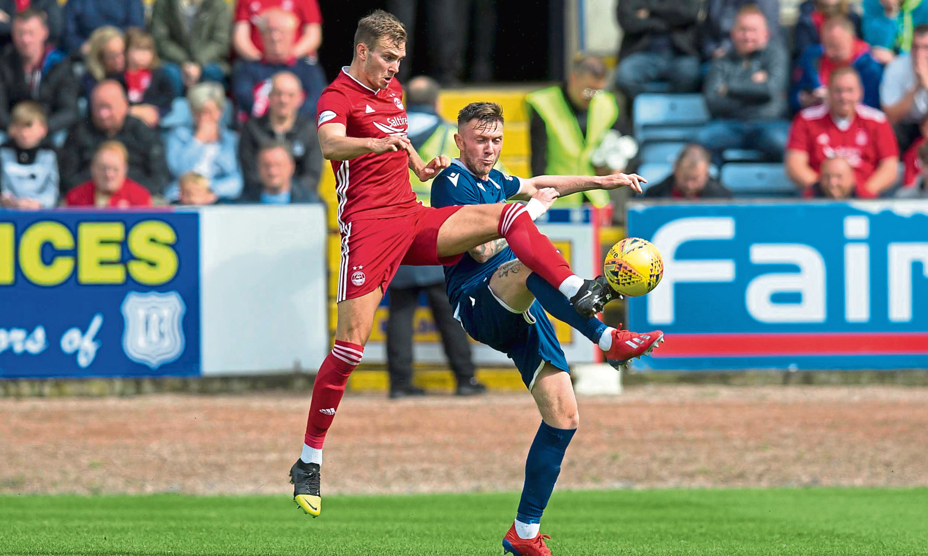 Ryan Hedges of Aberdeen challenges for the ball with Jordan McGhee of Dundee.