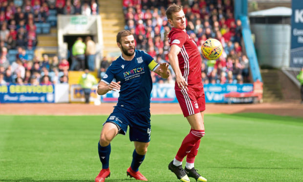 Dundees Jamie Ness pressures Ryan Hedges of Aberdeen on Saturday.,