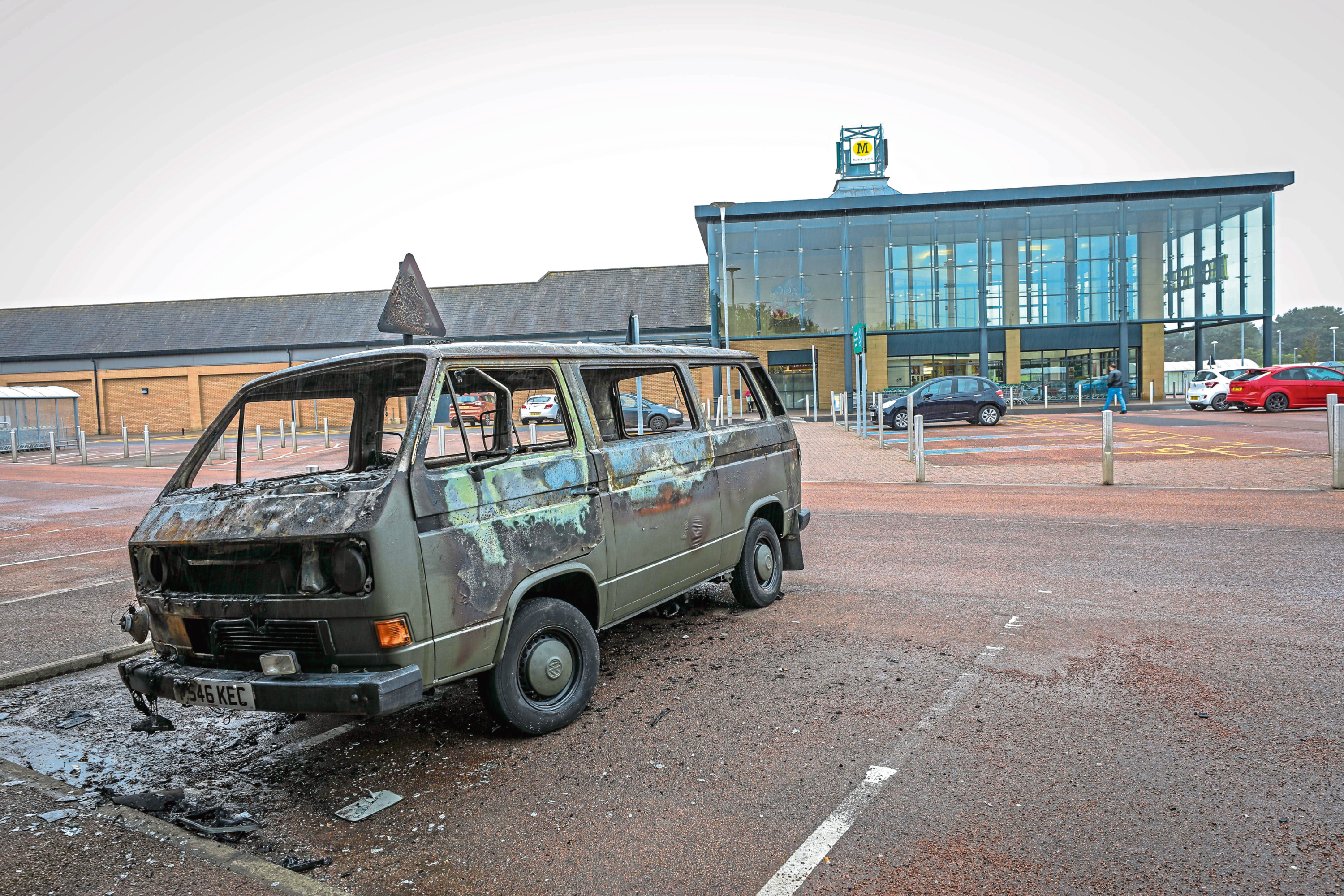 Remains of a VW Camper Van burnt out in the car park.