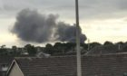 A plume of black smoke seen from a distance.