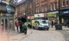 Police and paramedics helping a woman outside the Wellgate.