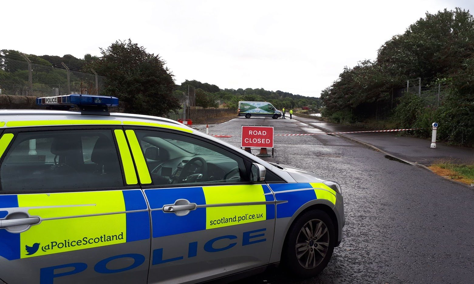 Police blocking off the road next to the flood.