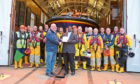 Father James presenting the cheque to Mr Smith, watched by members of Arbroath RNLI.