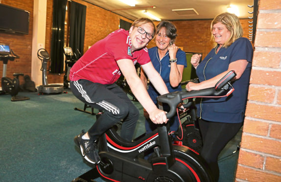 Michael Cook tries out the cycle machine cheered on by convener Fiona Cook and convener Anne Pannell.