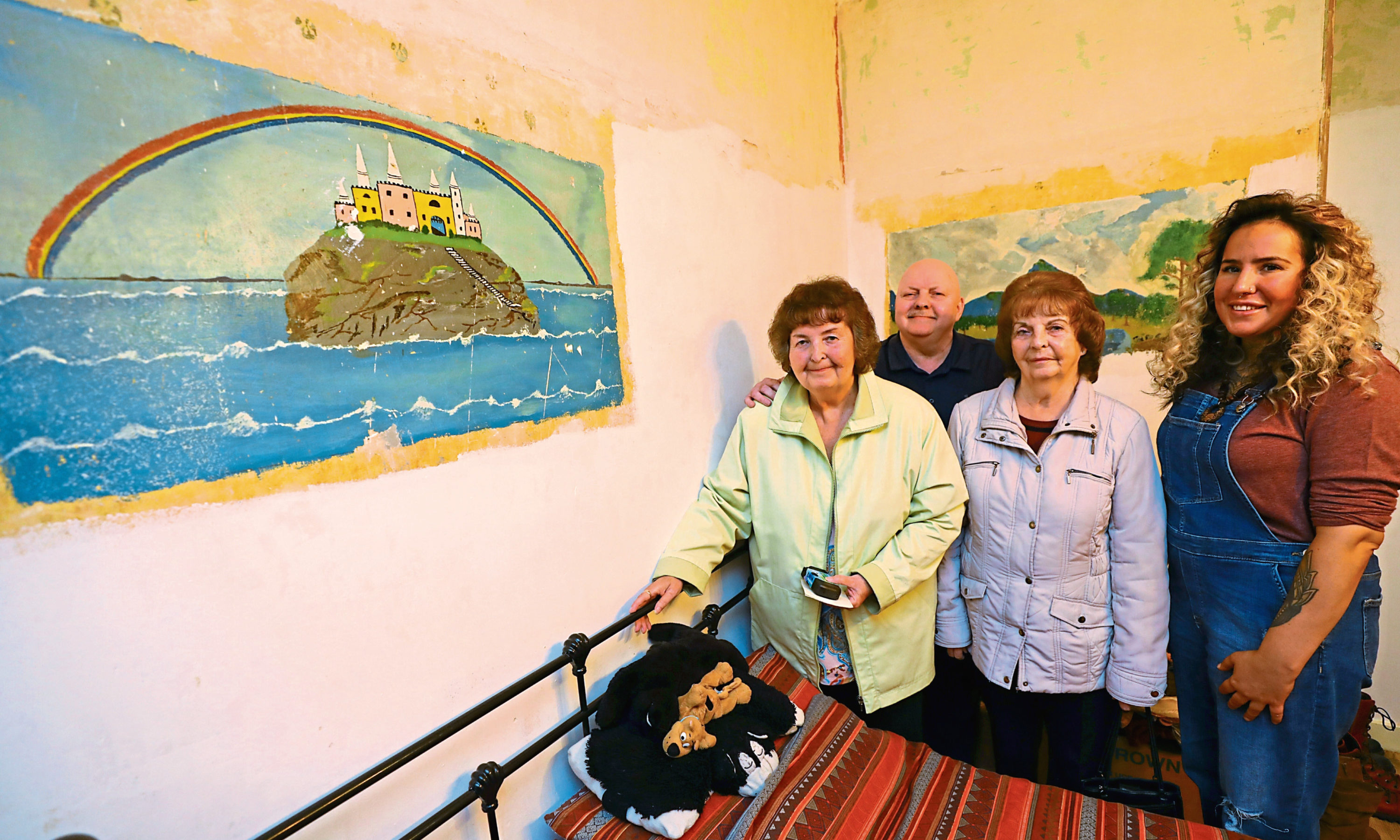Benjamin Hutton's family, from left, Catherine Andrews, Charles Hutton and Margaret McKee, with Sarah Graham, owner of the flat, beside the paintings on the wall.