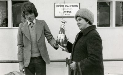An apprentice hands a bottle of champagne during a launch.