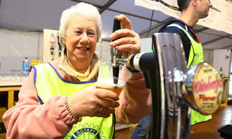 President of the Rotary Club of Dundee, Mary Crighton getting into the 'spirit' by pulling a pint.