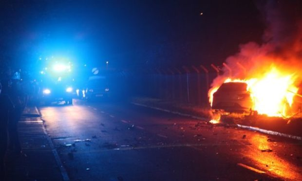 Police and the car which went on fire in last night's crash.